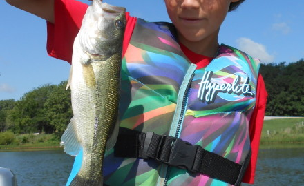 Drew Reese and one of the smallmouth bass he caught in Ontario, Canada in July. Read about his
