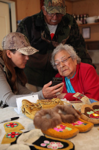 Elders from the Swampy Cree Nation looking at photos of my beaded skull art.