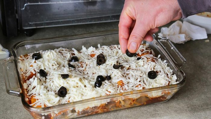 Top enchiladas with cheese and olives before baking. (Jenny Nguyen photo)
