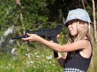 little girl aiming a big gun