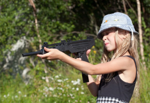 little girl aiming a big gun