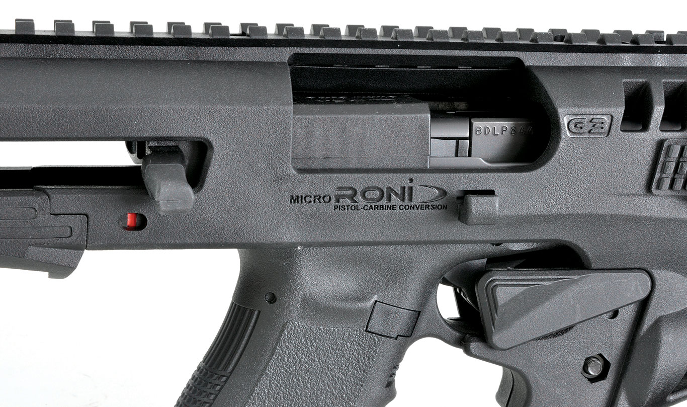 A closeup of the Glock inserted into the Micro RONI Stabilizer, wearing the charging handle.  Notice how huge the ejection port of the RONI is.