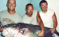 Nick Anderson (left) holds the 143-pound blue catfish he caught late Saturday. He was fishing with his dad, Rick (center) and brother Jeramie Mullis. (Mecklenburg News/Dallas Weston)