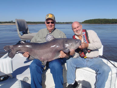 Owen Schroeder shows off his huge 83-pound blue cat with the help of guide James Patterson. Photo by Vernon Summerlin.