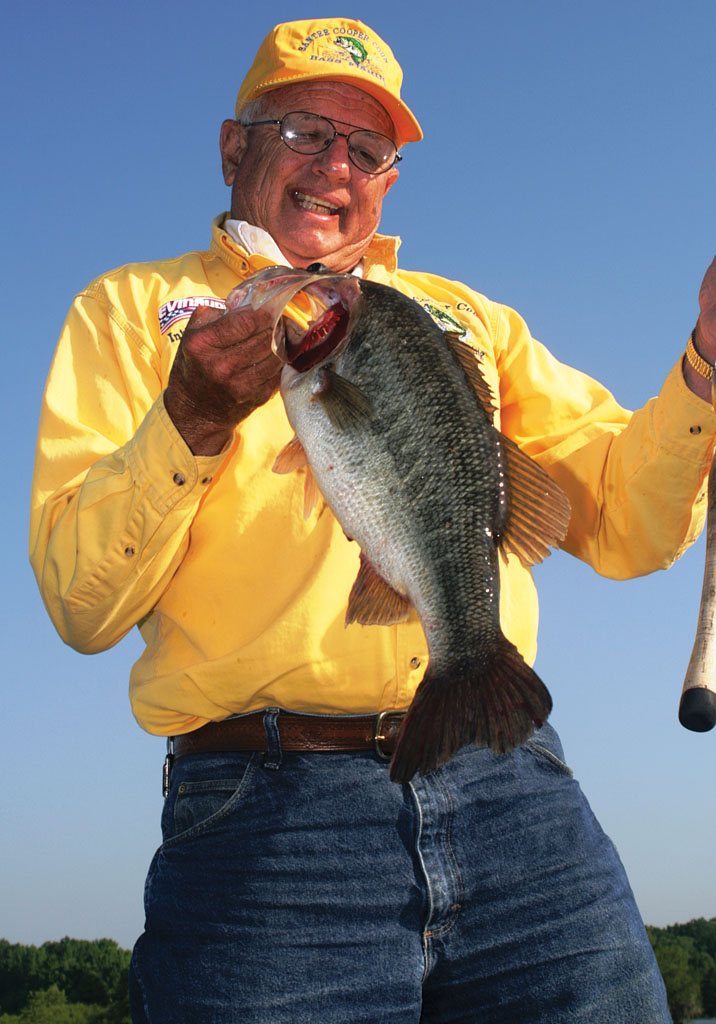 Guide Inky Davis hefts a Lake Marion largemouth taken in hot weather from heavy cover. Photo by Terry Madewell.