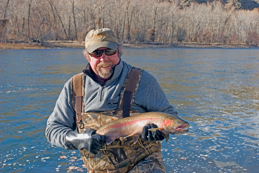 Fighting the cold water and the crisp air, Bill Mead shows off a keeper steelhead. Photo by Jim Foster.