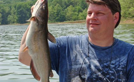 The author lifts a channel catfish caught near the bottom along a weedline in Patoka Lake near