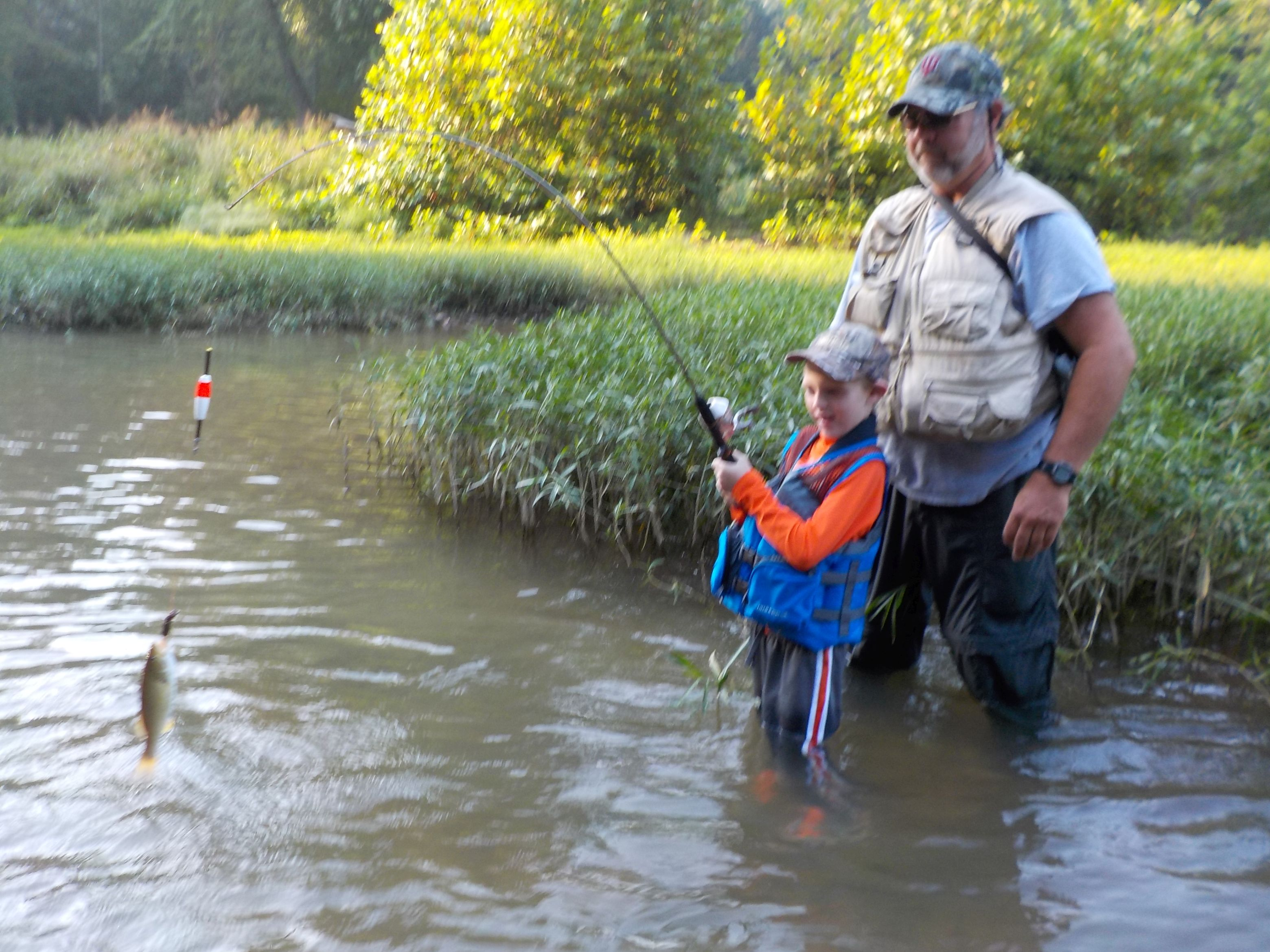 Three generations wading blue river game fish for River fishing games