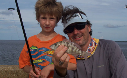 Danny, 7, and his father, John Geiger, with the smallest but most important fish caught during a