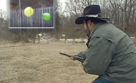 Trick shooter Bill Oglesby demonstrates aerial shooting; popping 3 balloons while shooting a rifle