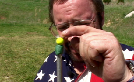 Trick shooter Bill Oglesby shoots a gumball downrange with a .22 caliber rifle and then plays a