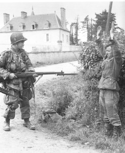 An American Airborne trooper holds a German prisoner under guard using his Garand fitted with an M1 bayonet. He is festooned with a variety of U.S. and German equipment.
