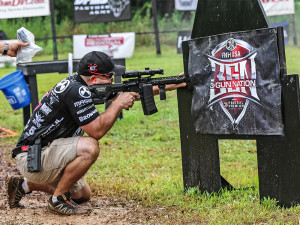 3-Gun Nation champion Rob Romero kneels in the mud to shoot around a barricade.
