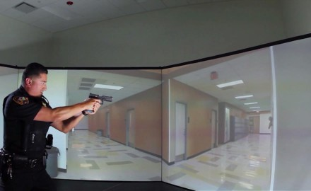 Patrick Sweeney is in the simulator with a police officer in a school shooting scenario.
