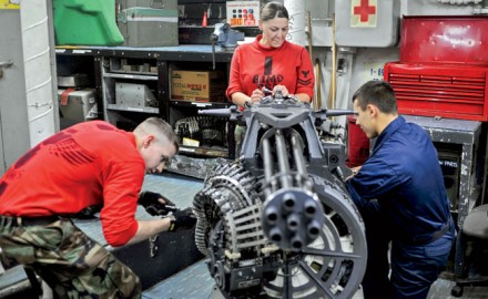 U.S. Navy Petty Officer 2nd Class Kimberly Rogers, center, supervises Seamen Aaron Deskins, left, and Tyler Tassio, as they work on an M-61A2 Vulcan 20mm Gatling gun in the aviation ordnance shop aboard the aircraft carrier USS George Washington in the Pacific Ocean, Oct. 25, 2011. Rogers is an aviation ordnanceman, Deskins is an airman and Tassio is an aviation ordnanceman airman. Photo Courtesy of DOD