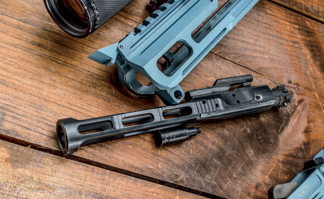The bolt carrier receives lightening cuts and rides within a skeletonized upper receiver.