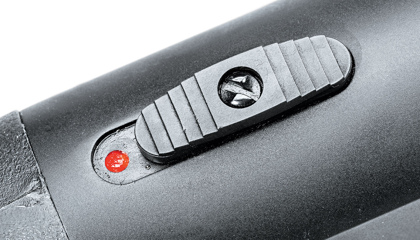 The safety is deactivated by sliding it forward, which reveals a painted red dot fire indicator.