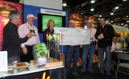 Curt Price, president of the Burt Coyote Co., presents a check for more than $15,000 to Mary Hale of The Pink Arrow Project at the 2012 Archery Trade Show in Columbus, Ohio.