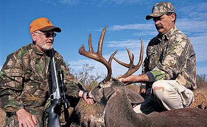Guide Chuck Booth (right) and the author made a long, tense stalk of this buck on the Herbst Ranch in Texas. The men spotted the 9-pointer and several other bucks in pursuit of a doe, and a shot eventually was offered. Few other forms of whitetail hunting can match this for sheer drama. Photo by Dr. James C. Kroll.