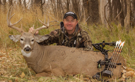 The author, Mark Kayser, admires a buck taken near the ranch house mentioned in the article.  Dogs