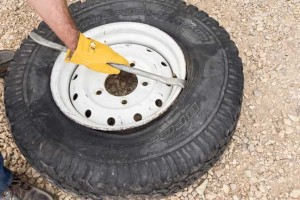 11) Hook one tire iron under the bead and pry it over the rim.
