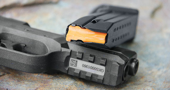 The gun features an accessory rail up front, and the magazines' bright orange followers are a big help in assessing the gun's condition.